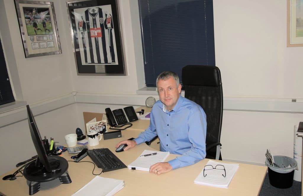 A Windsor sitting at his desk