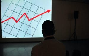 a shadow of a man infront of a graph