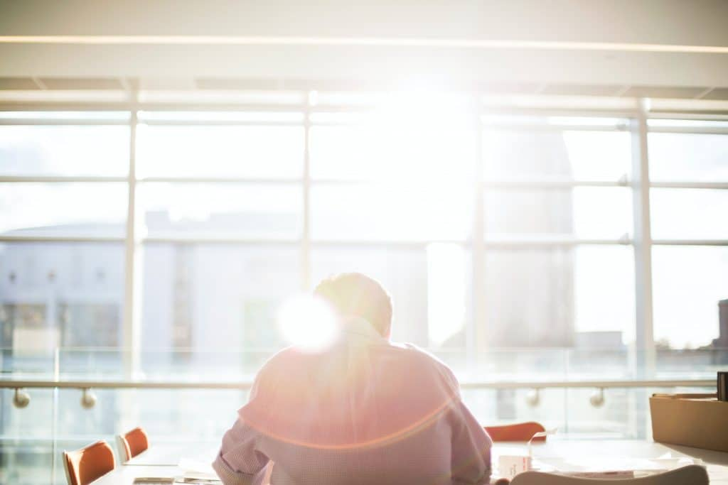 Man working at a desk by a window with the sun coming in