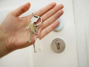 A man holding a house key and keyring