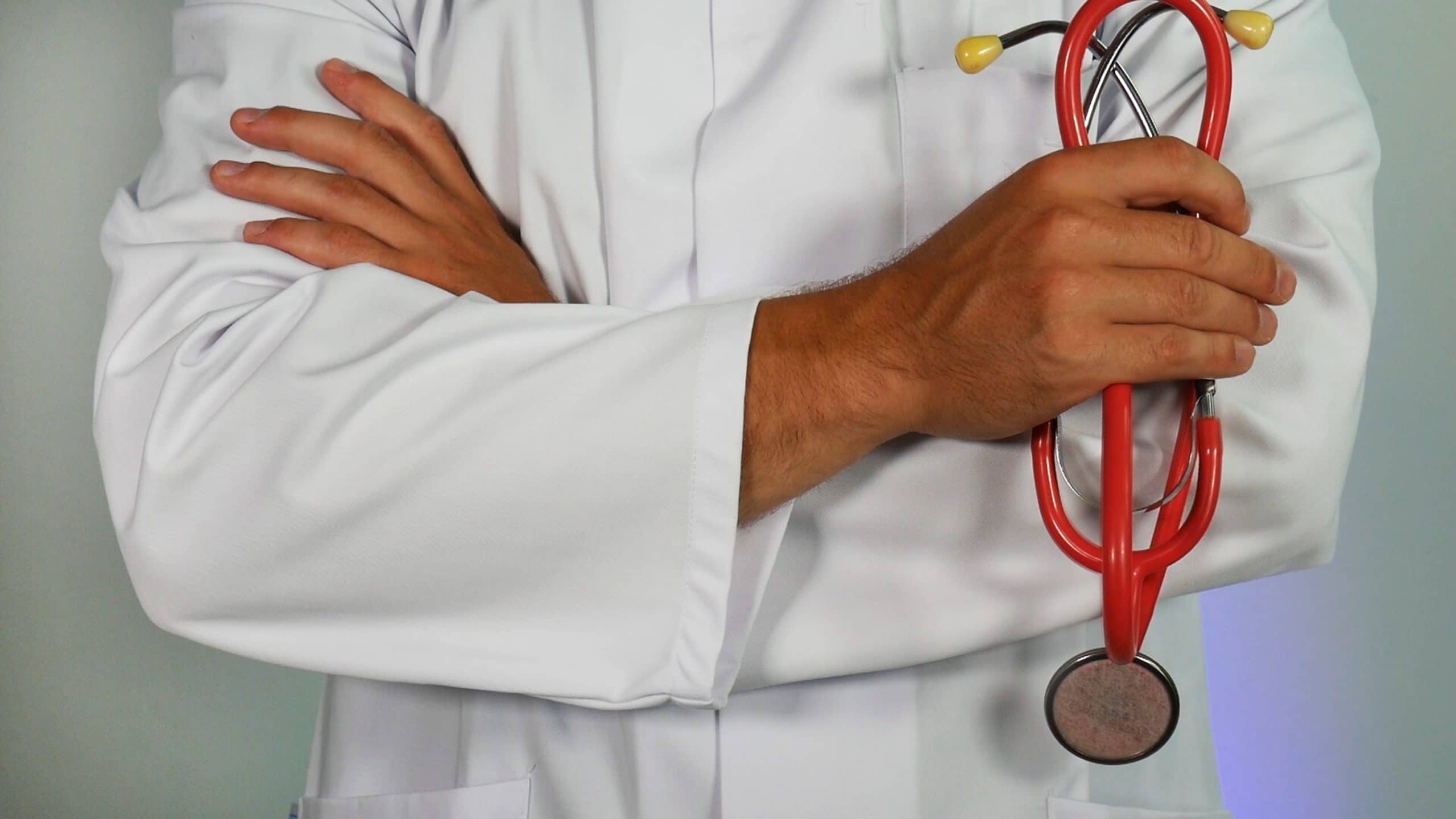 A man in a white coat holding a stethoscope